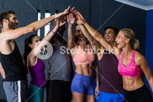 Athletes stacking hands in fitness studio