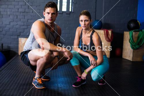 Confident athletes crouching in fitness studio