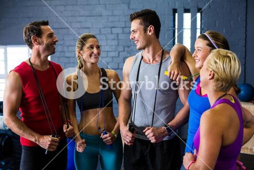 Athletes with jump rope standing against wall in gym