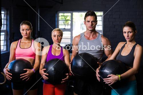 Determined athletes with fitness ball