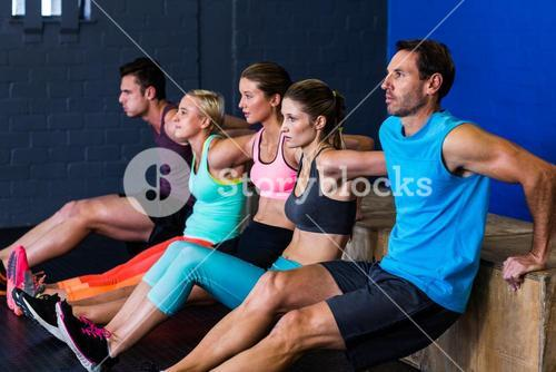 Athletes exercising on wooden box