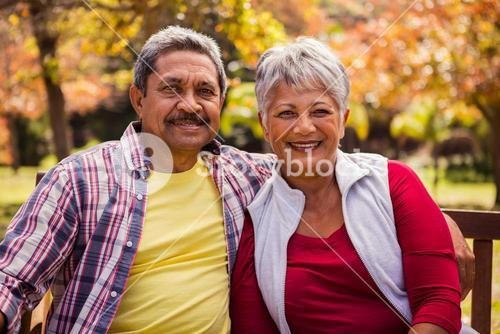 An elderly couple smiling at the camera sitting on the bench