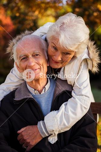 An elderly woman hugs her husband sitting on the bench looking at camera
