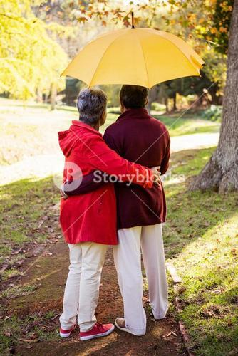 Couple holding umbrella while embracing