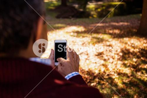 Man using cellphone in park