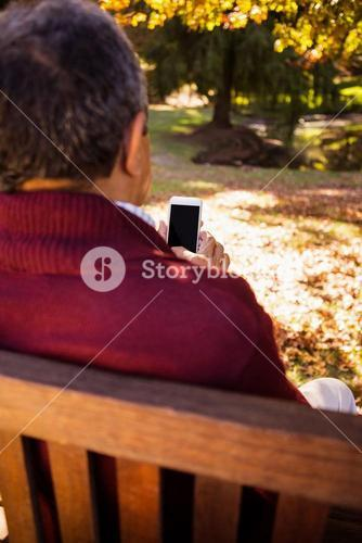 Man using cellphone while relaxing on bench