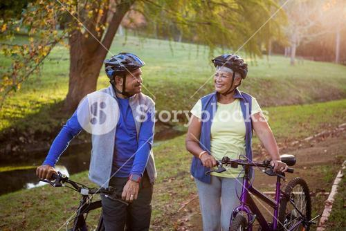 Mature couple walking with their bike