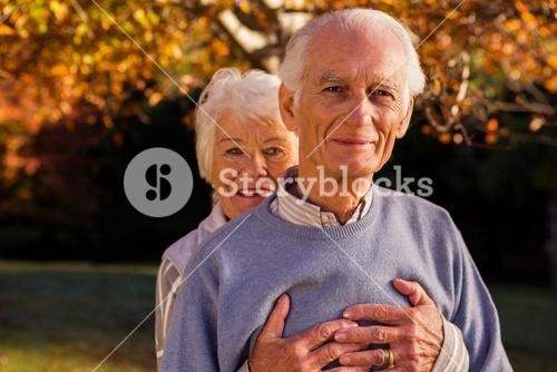 Senior couple embracing with the woman behind