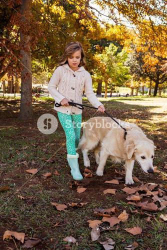 Little girl taking for a walk her dog
