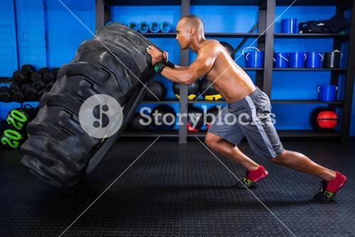 Side view of male athlete pushing tire