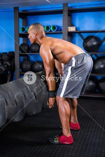 Side view of male athlete picking up tire