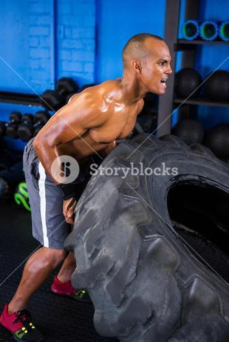 Aggressive male athlete pushing tire in gym