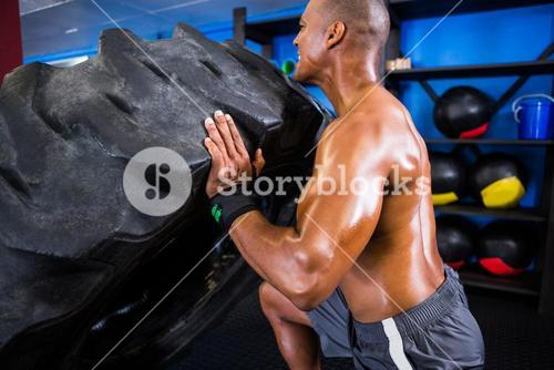Shirtless athlete pushing tire