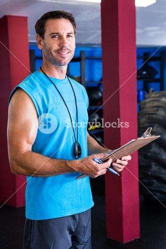 Smiling fitness instructor holding clipboard