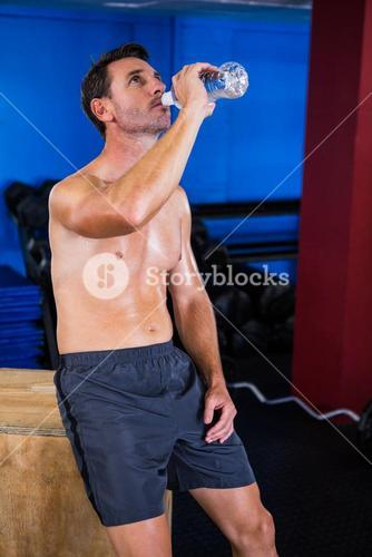 Shirtless athlete drinking water in gym