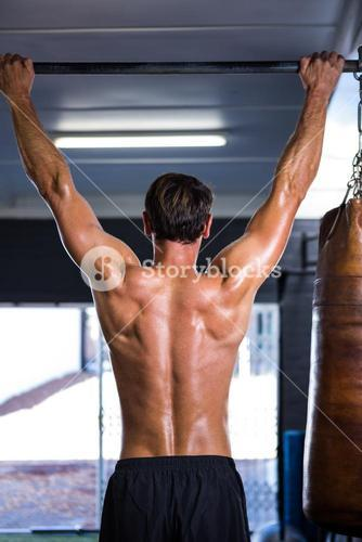 Rear view of shirtless athlete doing chin-ups