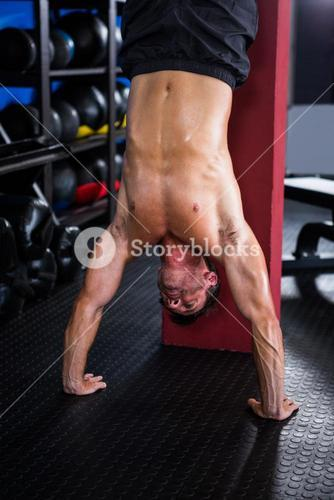 Shirtless athlete doing handstand