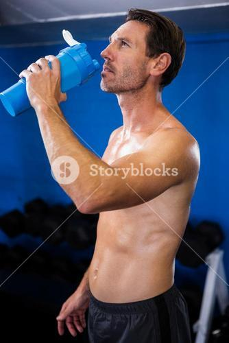 Shirtless young man drinking water in gym