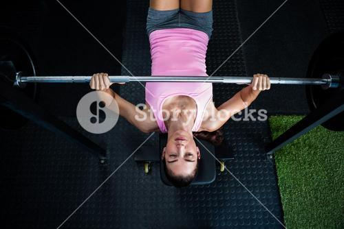High angle view of athlete holding barbell while lying on bench press