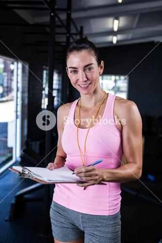 Happy fitness instructor holding clipboard in gym