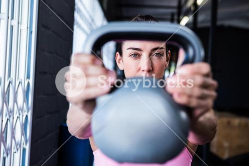 Serious female athlete lifting kettlebell in gym