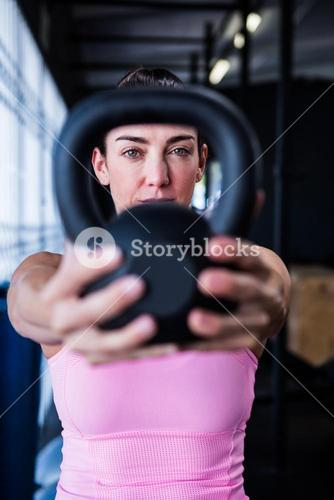 Portrait of serious athlete showing kettlebell