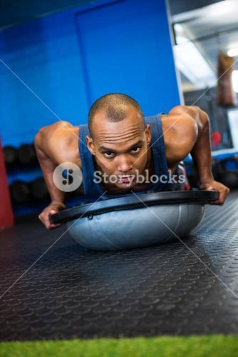 Portrait of serious athlete with BOSU ball in gym