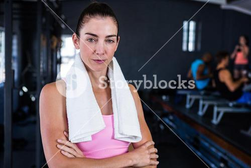 Portrait of serious female athlete with arms crossed