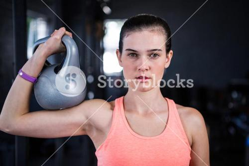 Portrait of serious female athlete holding kettlebell in gym