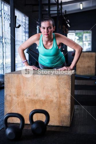 Portrait of young athlete using wooden cube in gym