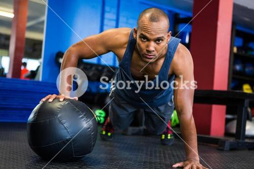 Serious man doing push-ups with exercise ball