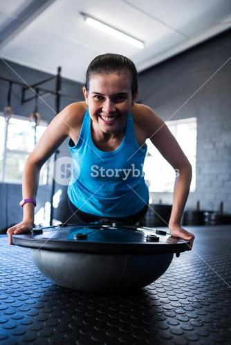 Smiling athlete with BOSU ball in gym