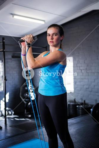 Portrait of serious female athlete stretching resistance band