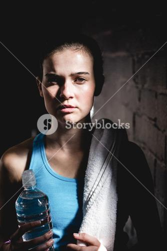 Serious female athlete holding water bottle
