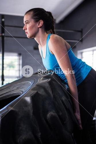 Female athlete pushing tire in gym