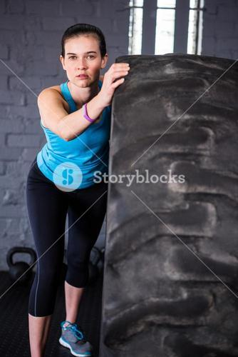 Portrait of confident female athlete pushing tire in gym