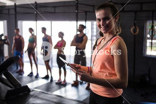Happy female fitness instructor holding clipboard