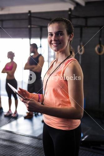 Portrait of happy female fitness instructor holding clipboard in gym