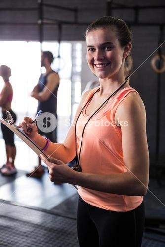 Cheerful female fitness instructor holding clipboard in gym