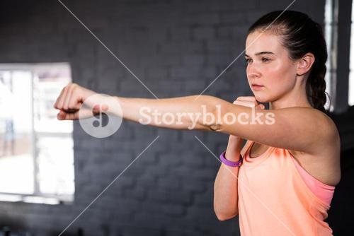 Young woman punching in gym