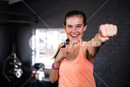 Smiling young woman punching in gym