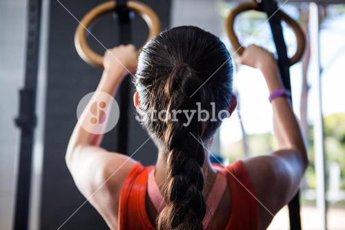 Rear view of female athlete holding gymnastic rings