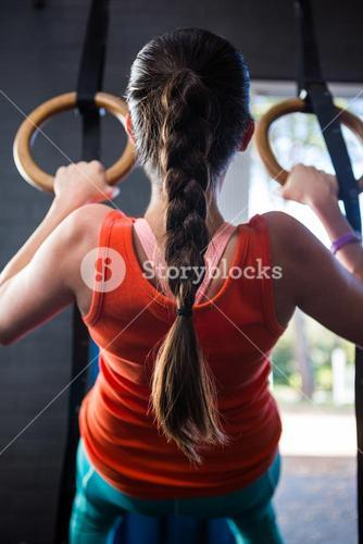 Rear view of young athlete holding gymnastic rings