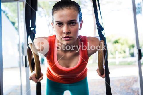 Portrait of confident athlete holding gymnastic rings