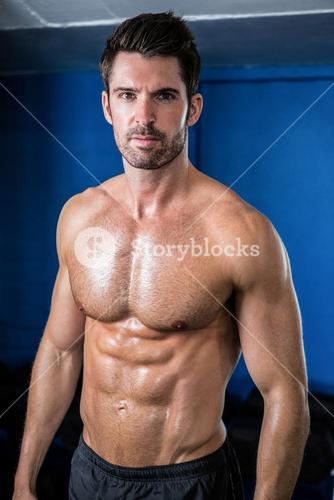 Portrait of shirtless male athlete in gym