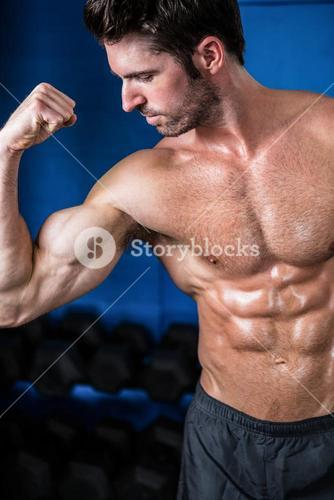 Shirtless athlete flexing muscles in gym