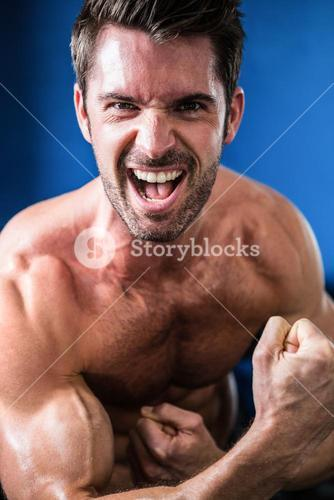 Portrait of cheerful shirtless athlete flexing muscles