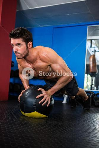 Shirtless athlete exercising with ball