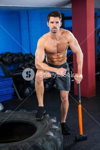 Shirtless young athlete with sledgehammer in gym