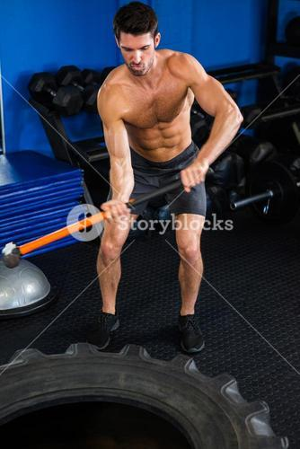 Shirtless man exercising with sledgehammer